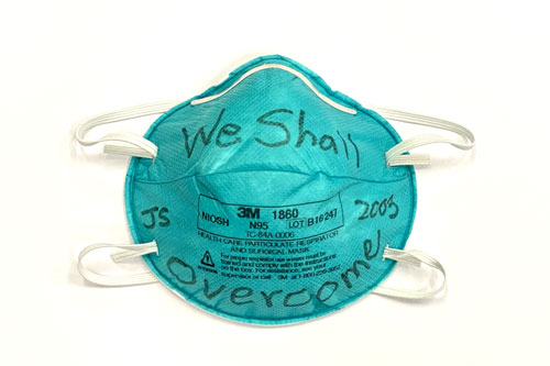 "The original N95 mask Prof. Joseph Sung and his team wore during SARS in 2003. On it, Prof. Sung wrote ""WE SHALL OVERCOME""."